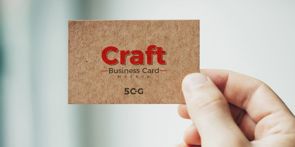 Free Man Holding Craft Business Card Mockup PSD