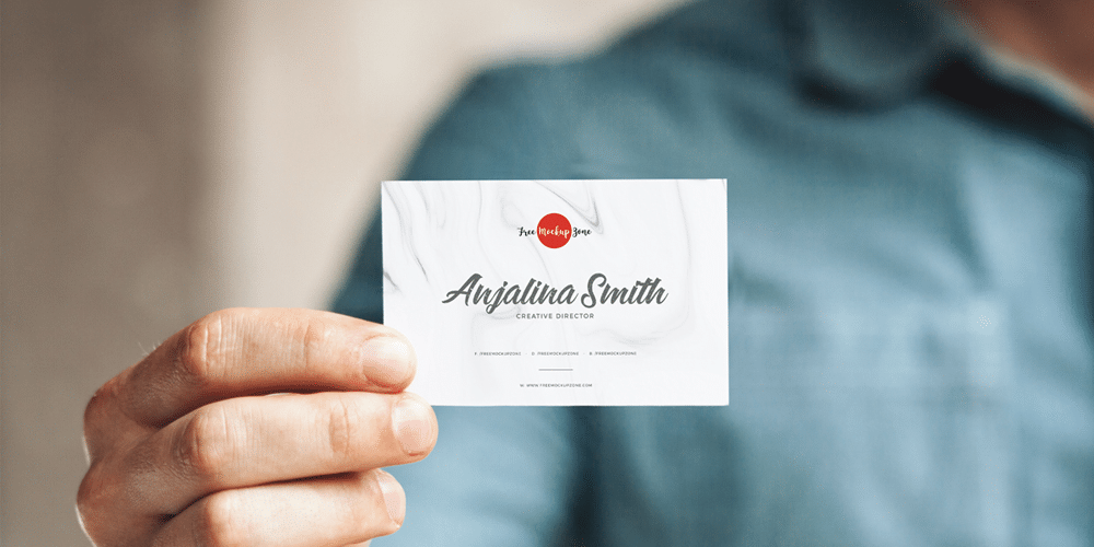 Free Man Holding in Hand Business Card Mockup PSD